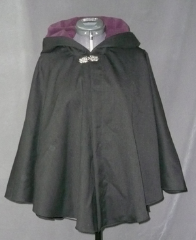 "Cloak:1746, Cloak Style:Full Circle Short Cloak, Cloak Color:Heathered Black, Fiber / Weave:Tropic Weight Wool, Cloak Clasp:Florentine - Medium, Hood Lining:Dk Plum Poly Moleskin, Back Length:27"", Neck Length:19.5"", Seasons:Summer, Fall, Spring."