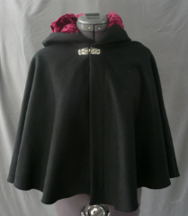 "Cloak:1773, Cloak Style:Shaped Shoulder-Short, Cloak Color:Black, Fiber / Weave:Wool Cashmere, Cloak Clasp:Alpine Knot - Silvertone, Hood Lining:Cranberry Crushed Velvet, Back Length:20.5"", Neck Length:20"", Seasons:Winter, Fall, Spring."