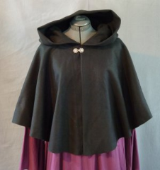 "Cloak:1943, Cloak Style:Full Circle Short Cloak, Cloak Color:Black, Fiber / Weave:Heavy Wool Melton, Cloak Clasp:Medallion, Hood Lining:Unlined, Back Length:24"", Neck Length:25"", Seasons:Winter."