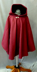Cloak:2163, Cloak Style:Cape / Ruana, Cloak Color:Wine, Fiber / Weave:Heavy Wool Melton, Cloak Clasp:Vale, Hood Lining:Black Cotton Velveteen, Back Length:36&quot;, Neck Length:23&quot;, Seasons:Winter, Fall, Spring, Note:Luxurious and warm, this felted<br>wool melton ruana  is a deep cranberry color.<br>The full size hood is lined<br>in black  cotton velveteen and a<br>sturdy pewter Vale clasp closes the front.<br>A cross between a cape and a cloak,<br>a ruana is a great way to keep warm when<br>frequent, unhindered use of your arms is needed..
