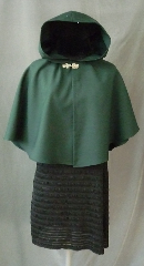 Cloak:2396, Cloak Style:Fuller Half Circle Child&#039;s, Cloak Color:Hunter Green, Fiber / Weave:Wool Gabardine, Cloak Clasp:Bavarian - Silvertone, Hood Lining:Unlined, Back Length:22&quot;, Neck Length:17&quot;, Seasons:Spring, Fall, Note:This short cloak is a fuller half circle.<br>The smaller neck makes this a good choice for a small child.<br>It is made from a deep green wool gabardine finished with a<br>silvertone Bavarian style hook and eye clasp.<br>Dry Clean or handwash cold, wrap in a towel and air dry..