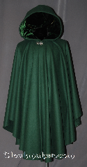 Cloak:2963, Cloak Style:Cape / Ruana, Cloak Color:Forest Green, Fiber / Weave:100% Wool, Cloak Clasp:Vale, Hood Lining:Green Velvet, Back Length:44&quot;, Neck Length:22&quot;, Seasons:Fall, Spring, Southern Winter, Note:This green ruana cloak is a gorgeous<br>forrest green with matching velvet lining.<br>Made of mid-weight with shortened sides<br>allowing for a a wide range of movement.<br>Perfect for driving on cold days.<br>Accented with a Silver tone Vale hook-and-eye clasp.<br>Dry Clean only..