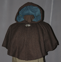 Cloak:2966, Cloak Style:Shaped Shoulder Cloak - Short, Cloak Color:Brown, Fiber / Weave:80% Wool / 20% Nylon, Cloak Clasp:Vale, Hood Lining:Teal Moleskin, Neck Length:19&quot;, Seasons:Fall, Spring, Southern Winter, Note:Perfect Starter cloak for a child or a<br>fashionable alternative to a shawl.<br>This dark brown short cloak is a<br>wool blend that is accented with<br>a silver tone vale hook and eye clasp<br>to complete the look for cool evenings.<br>A fun addition to any wardrobe.<br>Dry Clean Only..