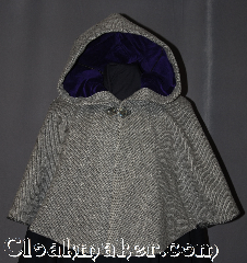 Cloak:2996, Cloak Style:Short Full Circle, Cloak Color:Grey and Black Chevron, Fiber / Weave:50% Wool / 50% Silk, Cloak Clasp:Grey Mother of Pearl button, Hood Lining:Purple Cotton Velveteen, Back Length:21&quot;, Neck Length:26&quot;, Seasons:Fall, Spring, Southern Winter, Note:Dense and warm for cool evenings,<br>this grey and black chevron<br>short cloak is made of a<br>wool silk blend and will<br>stop people in their tracks.<br>One of a kind and machine washable<br>with a grey Mother of Pearl button and<br>two hand warmer pockets<br>on the inside for added comfort.<br>The hood is lined in a<br>rich jewel tone purple<br>made of soft cotton velveteen<br>for a perfect addition to any outfit..