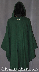 Cloak:3331, Cloak Style:Shaped Shoulder Ruana Cloak<br>with wand pocket, Cloak Color:Hunter Green, Fiber / Weave:100% Wool Melton, Cloak Clasp:Vale, Hood Lining:Long pile brown velvet, Back Length:45&quot; back<br>31.5&quot; overarm, Neck Length:21.5&quot;, Seasons:Fall, Spring, Southern Winter, Winter, Note:The wizard&#039;s special ruana cloak with<br>hidden wand pocket in the front edge.<br>A cross between a cape and a cloak,<br>a shape shoulder ruana is a great way <br>to keep warm while frequent, unhindered<br>use of your arms is needed.<br>Made with  a fitted shoulder for less bulk<br>and a long pile brown velvet lined<br>hood with vale clasp closure.<br>Ruanas make great driving cloaks!<br>Handwash cold..