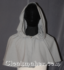 Cloak:3439, Cloak Style:Shape shoulder short, Cloak Color:Light Grey, Fiber / Weave:100% Wool, Cloak Clasp:Triskelion shank button, Hood Lining:Unlined, Back Length:14&quot;, Neck Length:21&quot;, Seasons:Fall, Spring, Summer, Note:A Perfect starter cloak for a child or a<br>fashionable alternative to a shawl.<br>This light grey short capelet is made<br>of a lightweight 100% wool fabric.<br>The simple celtic swirl and<br>loop clasp allows for<br>quick dressing on cool evenings.<br>Dry Clean Only..