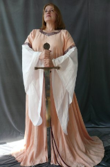 "Gown ID:G537, Gown Color:Peach, Style:12th Century, Sleeve:Long Drop Sleeve in white cotton, Trim:Celtic Knot at bicep, Neckline Type:Squared Sweetheart, Fabric:Linen, Sleeve Length:32.5"", Back Length:59""."