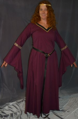 "Gown ID:G622, Gown Color:Burgundy, Style:12th Century, Sleeve:Long drop sleeve, Trim:Persian Style trim at bicep, black facing with gold braid on neck, Neckline Type:V-Neck, Fabric:95% Cotton, 5% lycra, Sleeve Length:32.5"", Back Length:55.5""."