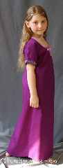 "Gown ID:G908, Gown Color:Orchid Purple, Style:Child Dress 12th century, Sleeve:Short Sleeve with Medallion, Narrow Purple & Pink trim, Trim:Medallion, Narrow Purple & Pink trim on sleeves, Neckline Type:Keyhole trimmed with pink ties, Fabric:Cotton, Sleeve Length:11.5"", Back Length:39."