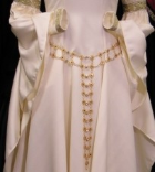 A woman's coin or chain belt made of gold tone metal pieces belting a custom order recreation accolade gown in ivory white.