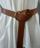 A man's brown leather ring belt with brass ring belting a white tunic.