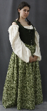 A woman models a historical recreation of a brown and green Irish bodice dress with lace up front.