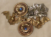 Several cloak clasps in a variety of metal finishes including silver, gold and brass including some mass produced and some handmade in zoomorphic shapes such as bats, floral designs such as roses and a round pair with blue stones.