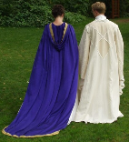 A couple dressed in custom made wedding garb consisting of a long purple cloak with gold trim and train and a white replica Saruman wizard's robe.