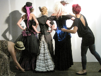 A group of models dressed for a steampunk themed photoshoot wearing corsets, bustles, overskirts, modern Victorian skirts, hats, goggles and jewelery in black, magenta, blue and white.