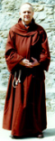 A man in a rust brown monk's robe with hood and rope belt..