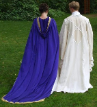 A couple dressed in custom-made wedding garb consisting of a long purple cloak with gold trim and train and a white replica Saruman wizard's robe.