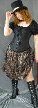 A woman modelling a steampunk outfit, which consists of a black top hat, a black overbust corset worn over a black blouse and a brown pattern modern Victorian skirt.
